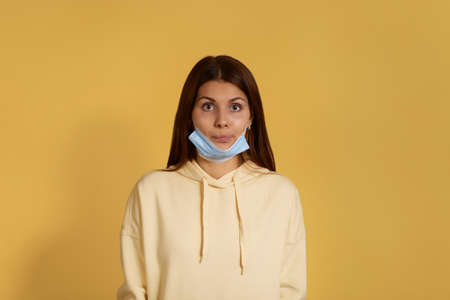 Puzzled young caucasian woman in yellow hoodie wears medical mask improperly on her chin, surprised with news, curious, comes to see doctor, has virus infection, isolated on yellow background 版權商用圖片