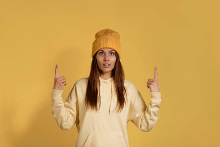 Ready for winter season, pretty caucasian woman in yellow hoodie wearing beanie looks in amazement, points upwards, sees amazing thing up, suggests click banner, isolated on yellow background 版權商用圖片