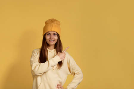 Ready for winter season pretty broadly smiling caucasian woman in a yellow hoodie wearing beanie points away on copy space, suggests follow a link, shows discount, isolated over yellow background 版權商用圖片