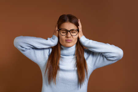 Stop it. Young caucasian woman wearing glasses and light blue sweater covers ears with palms and closes eyes tight, irritated with loud noise, has headache or migraine, isolated on brown background 版權商用圖片