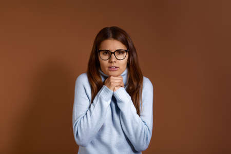 Its cold Displeased caucasian woman wearing glasses and light blue sweater keeps hands under chin, looks directly at camera, trembles, not prepared for chilly weather, isolated on brown background 版權商用圖片