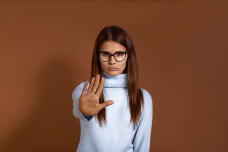 Stop here. Pretty serious caucasian woman wearing glasses and light blue sweater pulls palm towards camera, shows no, rejection gesture, refuses or says hold on, isolated on brown background