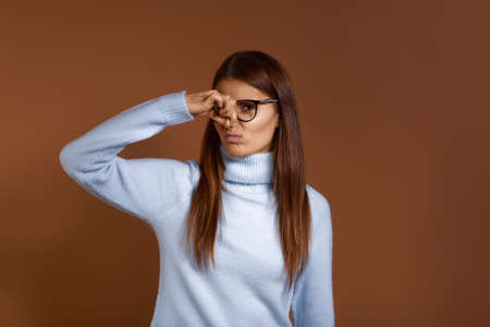 Young displeased caucasian woman wearing glasses and light blue sweater covers nose with hand, smells something bad, pinches nose, sees pile of garbage, feels bad odor, isolated on brown background