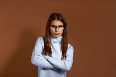 Skeptical displeased gloomy caucasian woman wearing glasses and light blue sweater keeps hands crossed over chest, looks from under forehead, expresses disagreement, isolated on brown background