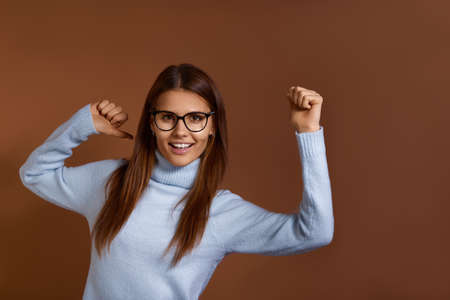 Lucky smiling caucasian woman wearing glasses and light blue sweater dances hands up, has fun, expresses positive emotions, freedom and happiness, feels like champion, isolated on brown background