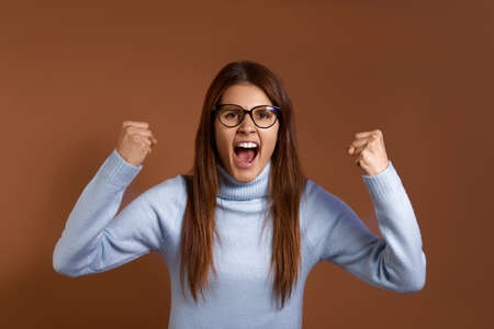 Triumph. Emotional cheerful caucasian woman wearing glasses and light blue sweater clenches fists excited of success. Joyful woman screams with happiness, achieved goals, isolated on brown background