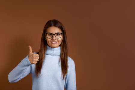 Young caucasian woman wearing glasses and light blue sweater shows thumb up, agrees on something, says okay, like gesture, accepts plan, approves an idea, looks positive, isolated on brown background 版權商用圖片