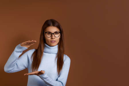 Young caucasian woman wearing glasses and light blue sweater shows big size of present, shapes height of gift box with hands, shapes huge box, demonstrates increase, isolated over brown background 版權商用圖片