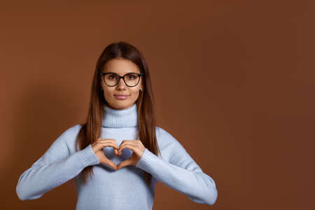 Smiling caucasian woman wearing glasses and light blue sweater confesses in love, makes heart gesture, shows her feelings, has happy expression, demonstrates sympathy, isolated on brown background