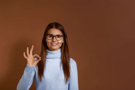 Smiling caucasian girl wearing glasses and light blue sweater makes okay gesture, says ok, agrees on something, confirms information, approves the plan, excellent result, isolated on brown background 版權商用圖片