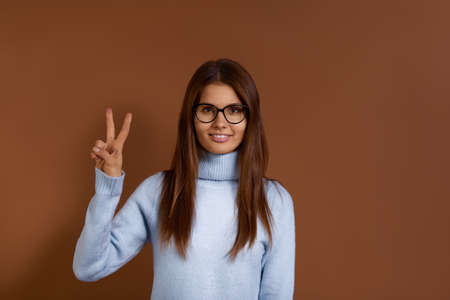 Lucky cheerful european girl shows victory or peace gesture, enjoys awesome day, sends positive vibes, smiling, dark hair, dressed in light blue sweater, wears glasses, isolated on brown background