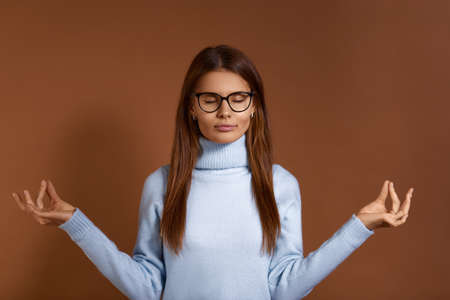 Peaceful beautiful european woman with dark hair wears glasses and light blue sweater, keeps hands in mudra gesture, eyes closed, practices yoga, meditation, relaxes, isolated on brown background