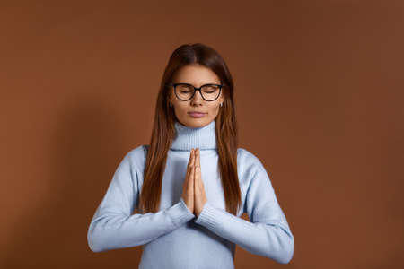 Peaceful beautiful european woman with dark hair wears glasses and light blue sweater, holds hands in namaste or prayer, eyes closed while practicing yoga and meditation, isolated on brown background