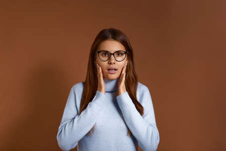 Surprised pretty caucasian female keeps palms near face, expresses amazement, has mouth open, can not believe in shocking news, wears glasses and light blue sweater, isolated on brown background 版權商用圖片