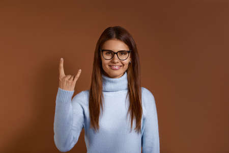 Excited punk young caucasian woman makes rock gesture, looks cool, expresses excitement and happiness, has appealing appearance, wears glasses and light blue sweater, isolated on brown background