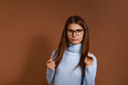 Pretty, confident young european woman with dark long hair wearing glasses and light blue sweater looks straight at camera, holding hair ends between fingers, isolated on brown background