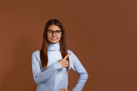 Pretty, smiling caucasian woman wearing glasses and light blue sweater blinks with eyes, indicates to right side on copy space, introduces new product, conducts webinar, isolated on brown background