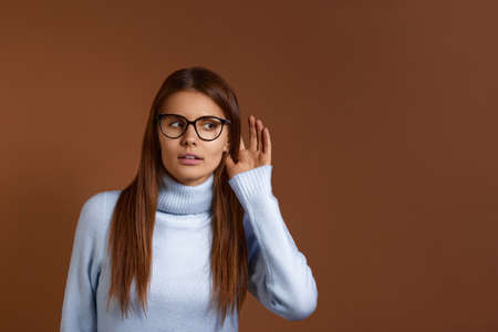 Curious caucasian woman wears optical glasses and light blue sweater, likes gossips, wants to hear secret information, keeps hand near ear, isolated on brown background, free copy space on the right
