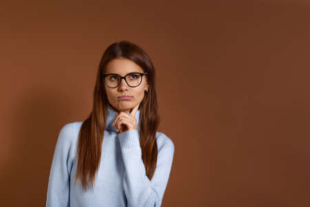 Young caucasian woman with dark hair wearing glasses and light blue sweater looks aside holding index finger under chin having doubt and suspicion, feeling sceptical, isolated on brown background