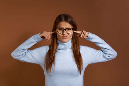 Annoyed, irritated, angry young caucasian woman wearing glasses and light blue sweater plugs her ears with fingers, can't stand loud noise, ignoring stress or conflict, isolated on brown background
