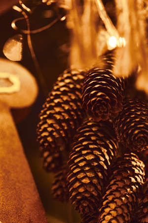 Cones and golden Christmas Fir Tree Decoration With Gold Ornaments with garland lights. 版權商用圖片