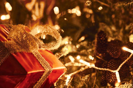 Horizontal photography of big red present with golden rustic style bow on Christmas Fir Tree with garland lights.