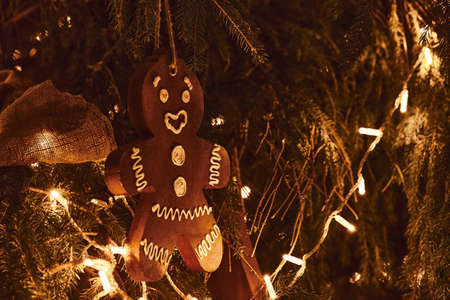 Gingerbread man and golden Christmas Fir Tree Decoration With Gold Ornaments with garland lights. 版權商用圖片