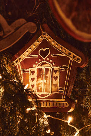 Vertical photography of Gingerbread house and golden Christmas Fir Tree Decoration With Gold Ornaments with garland lights.