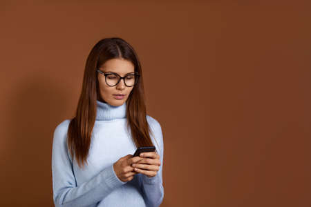 Serious attractive caucasian woman wearing glasses and light blue sweater holds mobile phone in hands, receives important message, copy space on the right, isolated over brown background 版權商用圖片