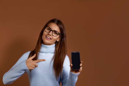 Joyful pretty caucasian woman wearing glasses and light blue sweater points with index finger at blank smartphone screen, advertises device, copy space on the right, isolated over brown background
