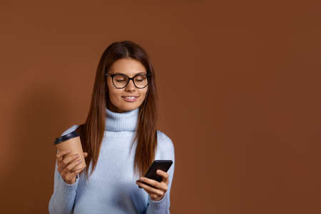 Cheerful smiling caucasian woman wearing glasses and light blue sweater holds coffee in one hand and mobile phone in the other, reading good news, chatting with friends, isolated on brown background