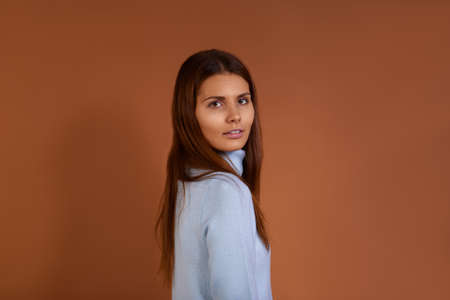 Pretty caucasian woman with dark long hair wearing light blue sweater stands sideways to camera, smiling gently, isolated over brown background