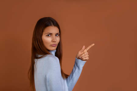 Pretty caucasian woman with dark long hair wearing light blue sweater stands sideways to camera, points with index finger at blank copy space, isolated over brown background
