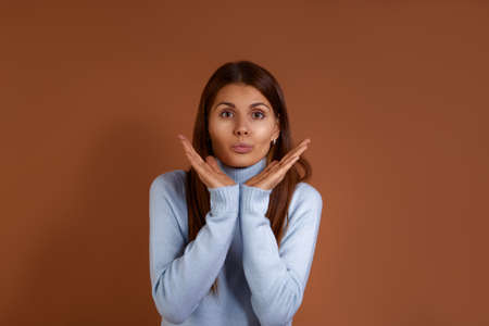 Air kiss. Beautiful caucasian woman wearing light blue sweater keeps palms together under chin, pouts lips, raises brows, has gladful expression, isolated over brown background