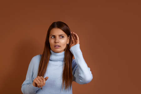 Curious caucasian woman wearing light blue sweater keeps hand near ear and listens private information, tries to overhear gossiping, has intrigued expression, isolated on brown background
