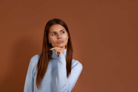 Sceptical caucasian woman wearing light blue sweater holding holds index finger under chin having doubt and suspicion feeling, thinks how to solve problem, isolated over brown background