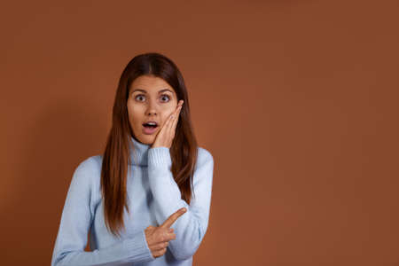 Inspired amazed beautiful caucasian woman wearing light blue sweater opens mouth, flattens cheek with one hand and points aside at free copy space with the other one, isolated over brown background