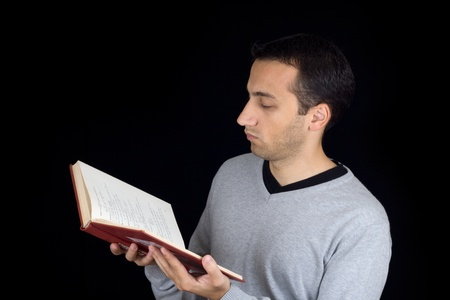 Portrait of an young man reading a book  isolated on black