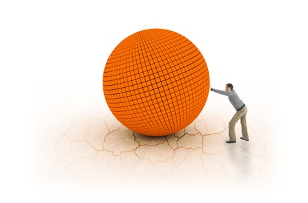 Young man pushing big and heavy ball on cracked earth