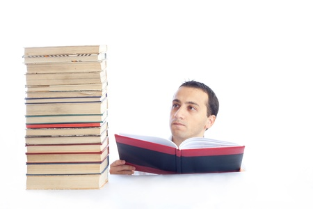 a young man with a pile of books reading one of them