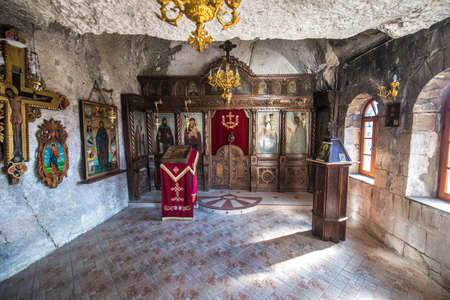 """Basarbovo, Bulgaria - March 11, 2018. The rock monastery """"St Dimitrii of Basarbovo"""", Bulgaria. Rock church. Iconography on rocks. Ancient church art. Inside interior."""