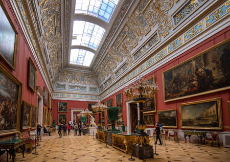 Saint Petersburg, Russia - 11 December, 2019: Interior of the Hermitage Russian state museum. Amazing room, walls and ceiling decorated with baroque gold ornaments. Largest in the world