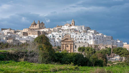 Panorama of Ostuni, Puglia, Brindisi, Italy. The picturesque old town and Roman Catholic cathedral and church Confraternity of Carmine. The white city in Apulia on the hill.