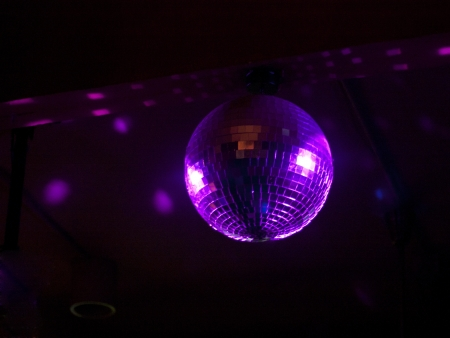Rotating Disco Ball Bathed in Purple Light against a black background