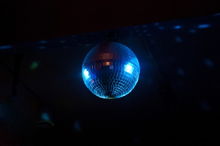 Rotating Disco Ball Bathed in Bluish Light against a black background Stock Photo