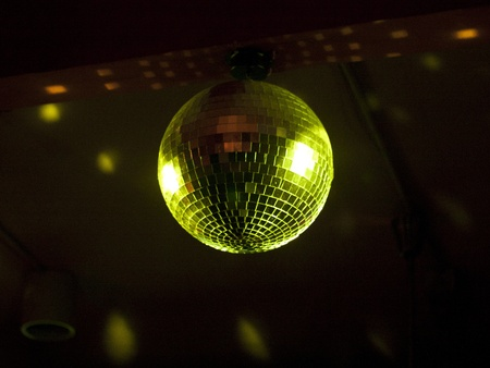 Rotating Disco Ball Bathed in Grenish Light against a black background Stock Photo - 8325030