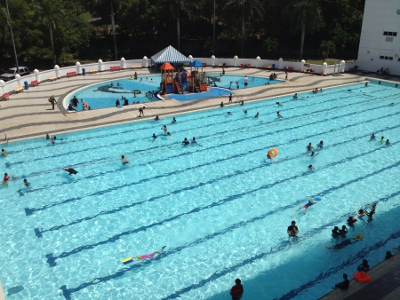 alam: crowd at a public swimming pool on a hot and sunny day