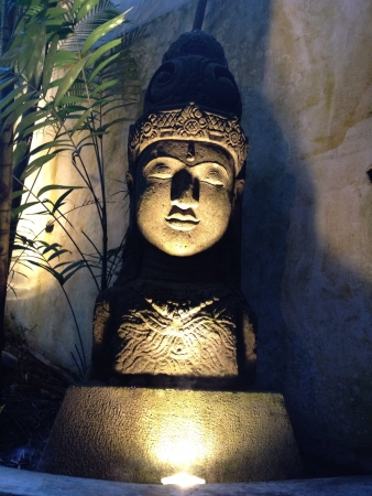 statue of the head of Buddha bathed in dramatic lighting Stock Photo