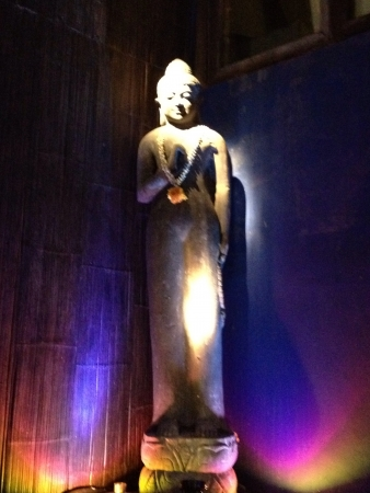 a statue of Buddha bathed in dramatic lighting