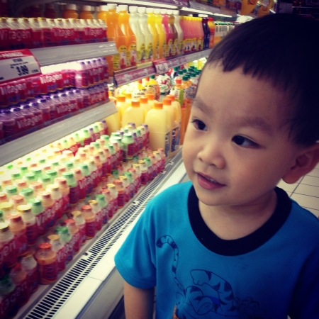 Happy smiling Chinese boy shopping at the grocery store supermarket